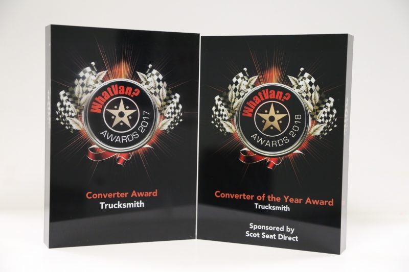 Two black resin awards bearing the What Van? Converter of the Year 2017 and 2018 logos, sit next to each other against a white background
