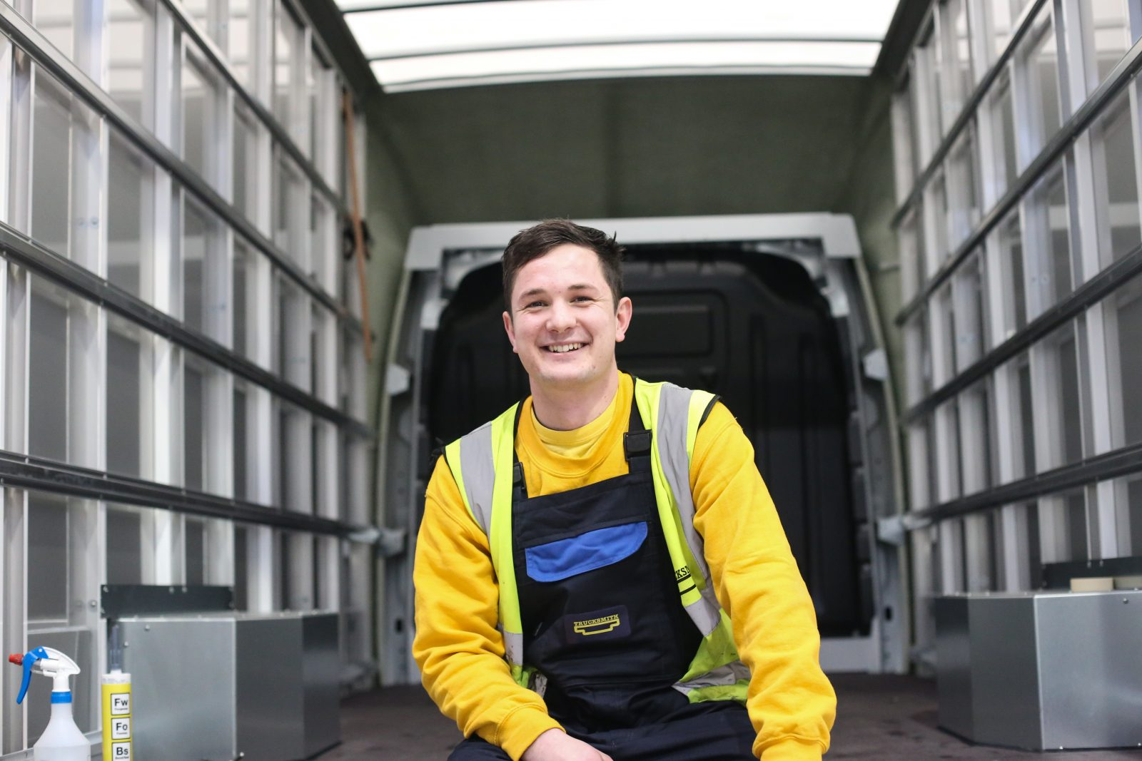 Trucksmith team member, Tylor, sits in the back of a LoLoader wearing his blue and yellow Trucksmith uniform.