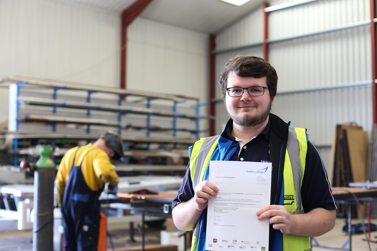 Trucksmith's Adam Barnett hold his acceptance to Exeter College letter whilst stood in an engineering workshop
