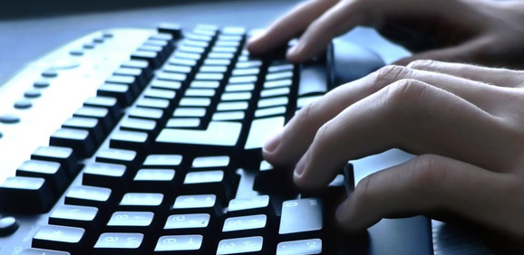 Fingers typing on a black keyboard